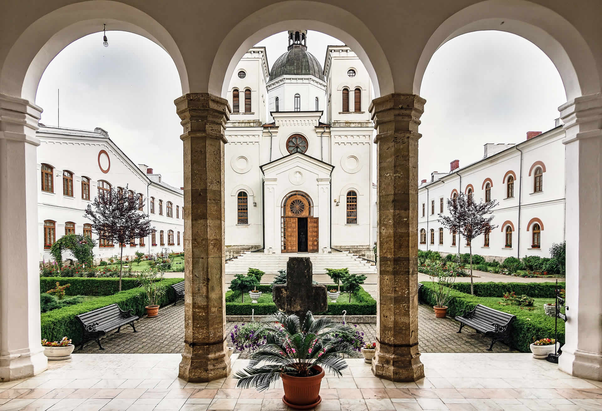 A  grandiose Italian monastery towers behind a small courtyard, with pristine hedgerows and two benches